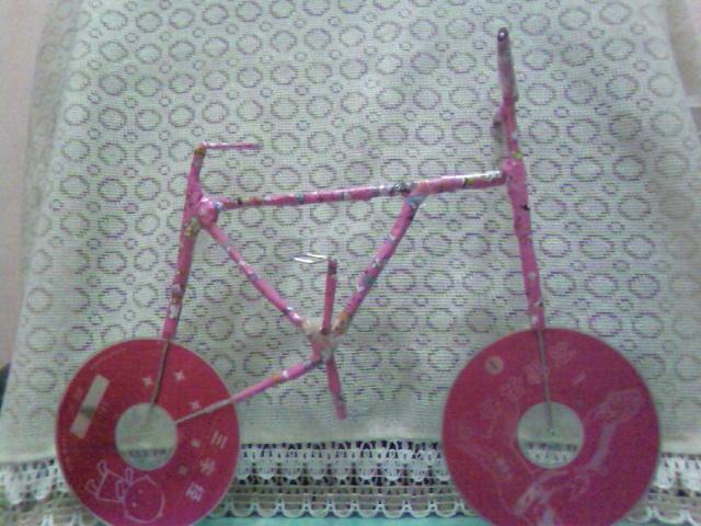 这是我的暑假作业,交一个手工小制作。妈妈上网帮我搜了一下,觉得用废旧光盘做个小自行车很漂亮,我们决定 这就动手制作。看,我这个自行车够漂亮吧!材料很简单,就是两张光盘,几个不用的窗帘钩,透明胶带,还有 包书皮用的纸。光盘我们选择了一个色系的两张粉色画面的 ,自行车的梁和架就是用窗帘钩做的哦,因为家里没有 铁丝、铝丝之类的东西,妈妈说窗帘钩是铝的,便于弯曲造型,就是长度不够,费了很大的劲 ,浪费了好多透明胶带 才把它们连接起来,捆绑固定。最后要归功的,就是那天买回来的包书皮,刚好也是粉色的,把自行车进行美